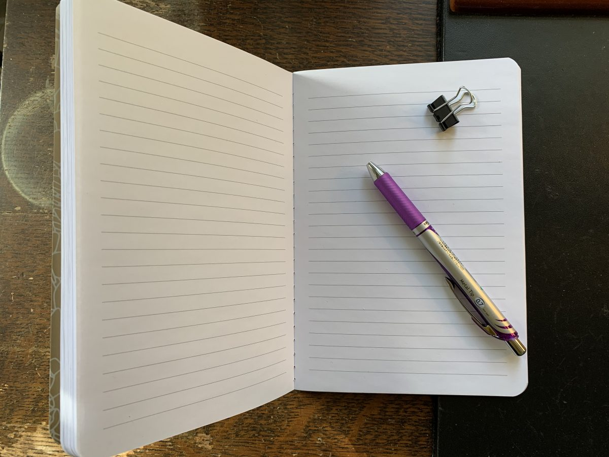 open notebook with binder clip and pen